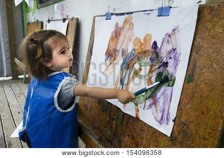 An adorable little girl painting and drawing.