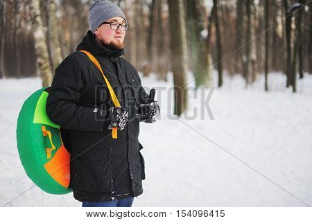 A young bearded guy with glasses walking with a pipe in the winter forest.