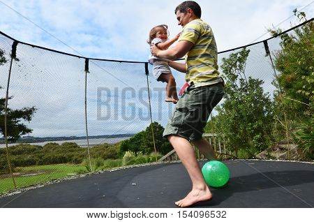Father and his baby jumping together on a trampoline.
