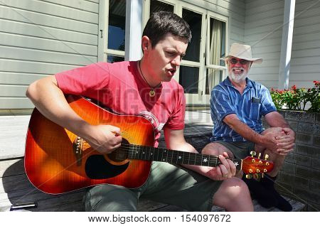 Portrait of handsome lad playing the guitar to his father.
