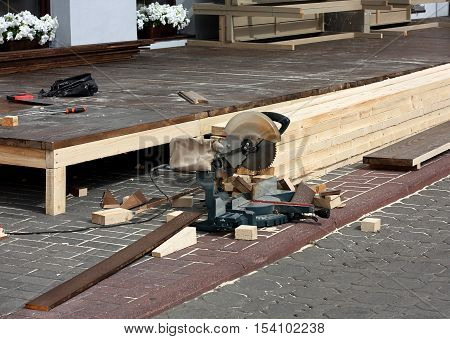 Circular saw white wooden slats - attributes of carpentry works produced in the street