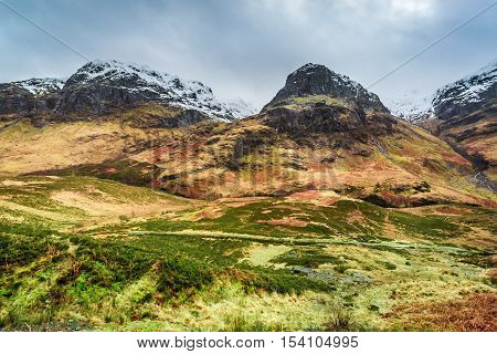 Mountains around Glencoe in winter in cloudy day