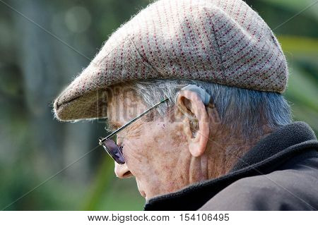 An Elderly man with a hearing aid.