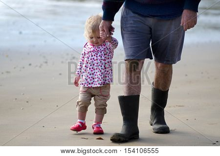 Grandfather with granddaughter walks on the beach during summer.