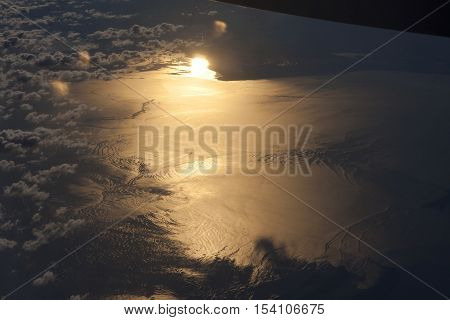 An Arial view of sun reflected on a body of water.