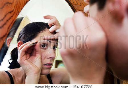Young caucasian woman looks in the mirror and plucks hair from her eyebrow.