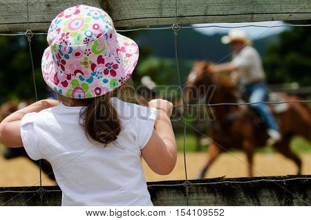 A little girl watches hoses at a rodeo show.
