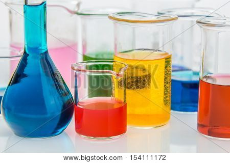 various beakers with different types of indicators in acids and basis four colors of indicators in several solusions