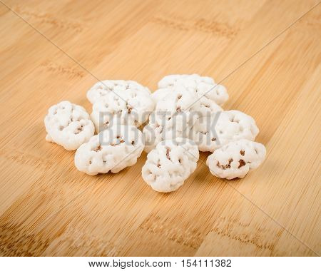 almonds in sugar on a wooden cutting board