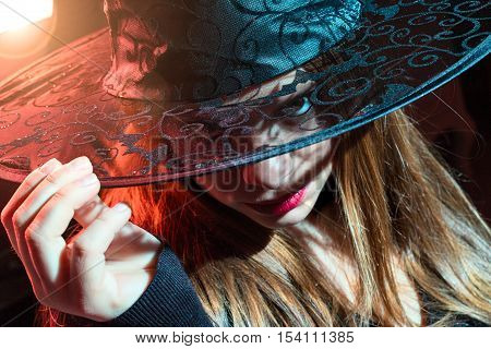 blond witch with lace hat in hand