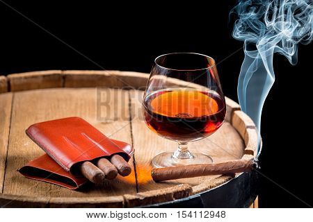Cognac In A Glass On Wooden Barrel