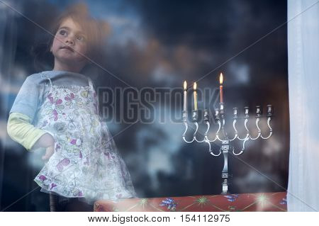 Hanukkah menorah with three burning candles on the second day of Hanukkah.