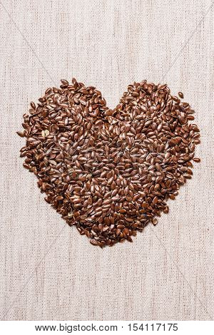 Diet healthcare healthy food. Raw flax seeds linseed heart shaped on sack burlap background.