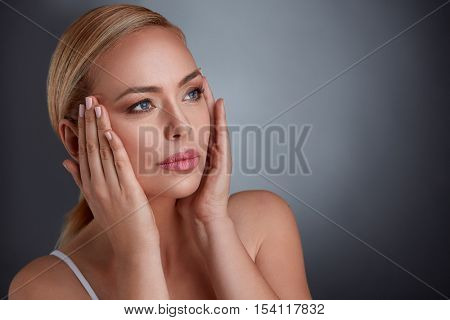 woman tightening skin on face to make you look younger, middle age and aging