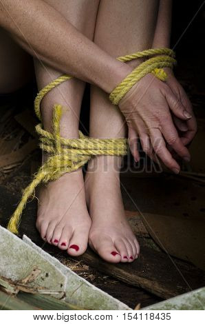Missing kidnapped abused hostage victim woman with hands and legs tied up with rope in emotional stress and pain afraid restricted trapped struggle terrified threaten locked in a cage cell.