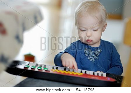 Little toddler girl playing toy piano at home