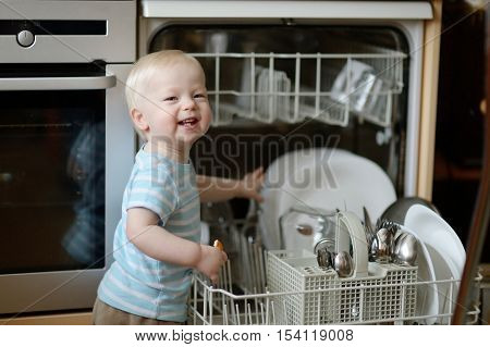 Mommy's little cheerful helper helping with a dishwasher