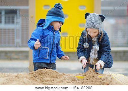 Two Kids Playing In A Sandbox