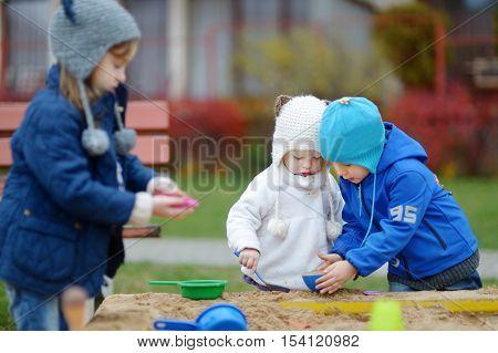 Three Kids Playing In A Sandbox
