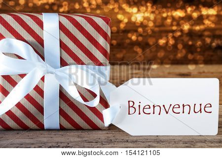 Macro Of Christmas Gift Or Present On Atmospheric Wooden Background. Card For Seasons Greetings, Best Wishes Or Congratulations. White Ribbon With Bow. French Text Bienvenue Means Welcome