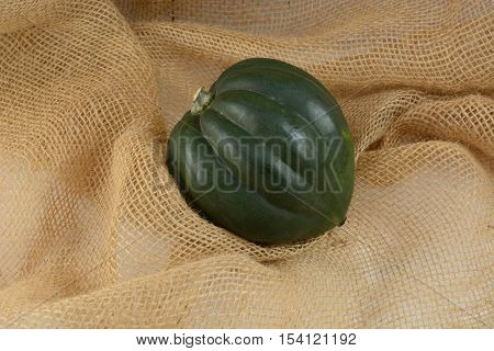 Raw whole uncooked acorn squash on burlap