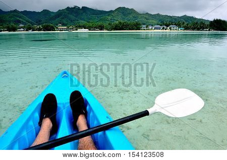 Young man kayaking in sea at over turquoise water during travel vacation in a tropical Island.Rarotonga Cook Islands.
