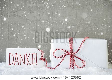 One Christmas Present On Snow. Cement Wall As Background With Snowflakes. Modern And Urban Style. Card For Birthday Or Seasons Greetings. Label With German Text Danke Means Thank You