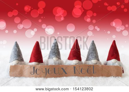 Label With French Text Joyeux Noel Means Merry Christmas. Christmas Greeting Card With Red Gnomes. Bokeh And Christmassy Background With Snow.