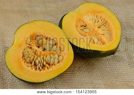 Raw uncooked acorn squash halves with seeds on burlap