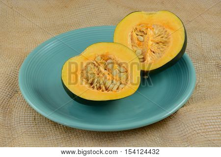 Raw uncooked acorn squash halves with seeds on blue plate