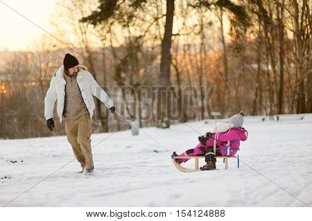 Young father and his two daughters having fun on winter day
