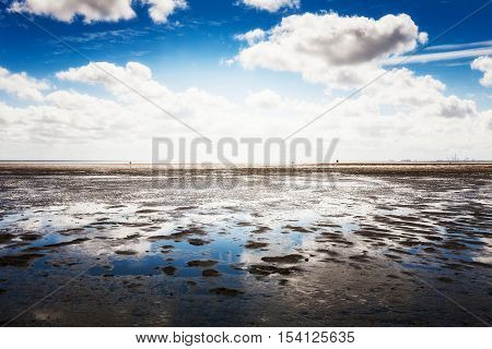 Mud flat at low tide. North sea landscape with cloud sky. Nature reserve and travel destination in Germany