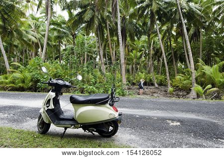 AITUTAKI - SEP 20:Tourist woman explore the nature with motorbike on Sep 20 2013.It's one of the must popular activity in the Island but Cook Islands Driver's License is required for motorized rental.