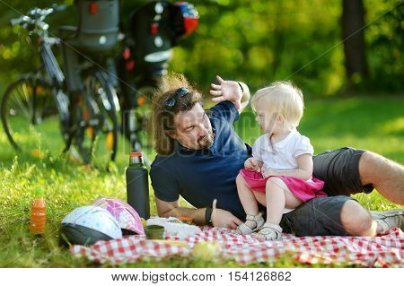 Young father and his daughter picnicking in the park