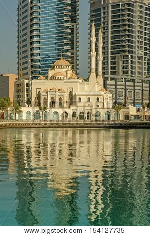 DUBAI, UAE - OCTOBER 09, 2016: A mosque with reflections in Dubai Marina.  Surrounded by tall unique skyscrapers with apartments and restaurants, the marina is open to The Gulf
