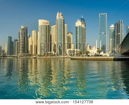DUBAI, UAE - OCTOBER 09, 2016: Dubai Marina is a man made marina stretching over 3km of land.  Surrounded by tall unique skyscrapers with apartments and restaurants, the marina is open to The Gulf