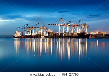 Containers loading by crane in the evening trade port shipping Shipping and logistic concept