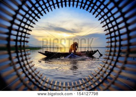 Silhouette fisherman throwing fishing net during sunrise