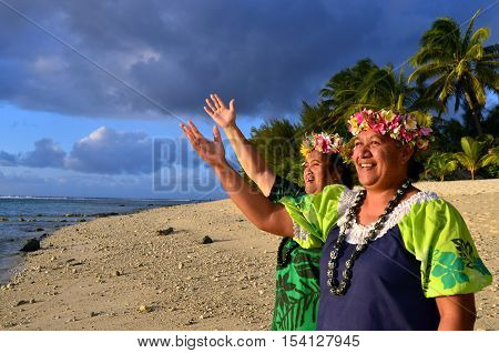 Portrait of two happy smily mature Polynesian Pacific islanders women on tropical beach with palm trees in the background.