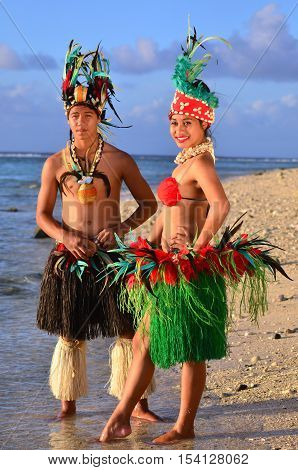 Portrait of attractive young Polynesian Pacific Island Tahitian male and female dancers in colorful costumes on tropical beach during sunset