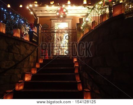 Christmas stairway lined with luminarias leading to decorated front door