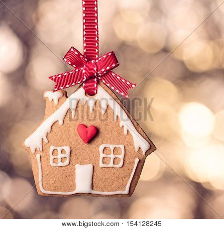 Hanging Gingerbread House Cookie decoration over warm bokeh background.
