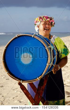 Portrait of mature Polynesian Pacific islanders woman sing and plays Tahitian Music with drum on tropical beach.