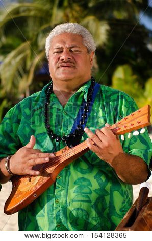 Portrait of mature Polynesian Pacific islanders man sing and plays Tahitian Music with Ukulele guitar on tropical beach with palm trees in the background.
