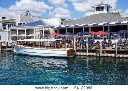 HARBOR SPRINGS, MICHIGAN / UNITED STATES - AUGUST 1, 2016: Tours of Little Traverse Bay, aboard the Pointer, embark from the side of Dudley's Deck restaurant.