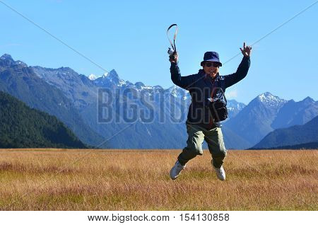 Happy tourist jumps in the air during travel to Fiordland and Milford Sound in the south Island on New Zealand.