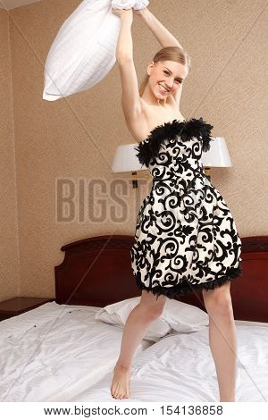 Stylish woman is standing on her knees on the bad and throwing pillow
