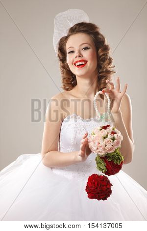 Pin-up bride with unusual bouquet.Professional make-up hair and style
