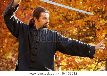 Adult man practicing Tai Chi with sword in autumn park