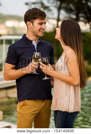 Young couple tasting wine near by the pool on a hotel